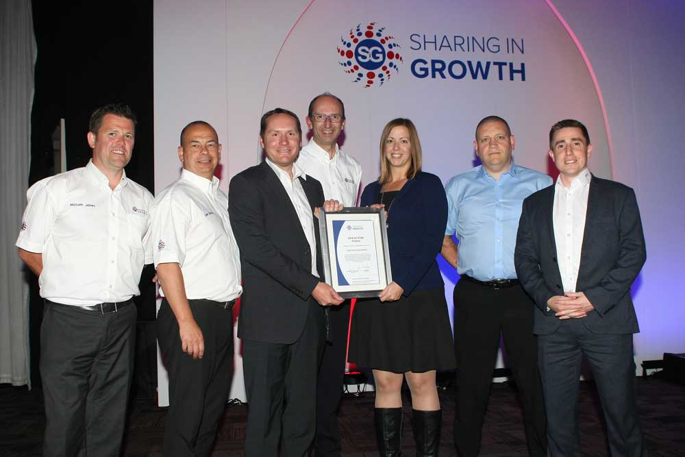 Poeton staff being presented with a certificate by Sharing in Growth team
