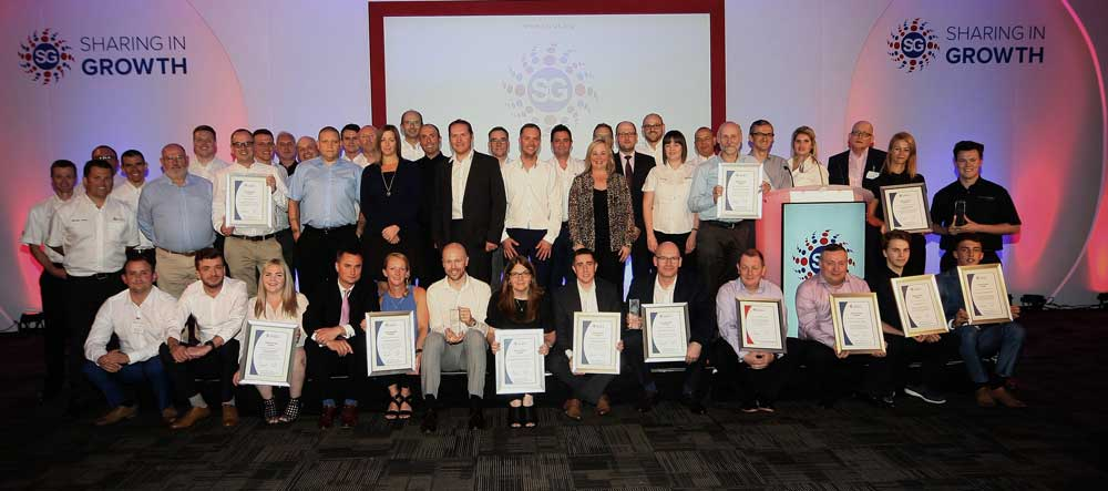 Group of people at Sharing in Growth presentation evening holding certificates