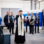 Priest giving a blessing in front of a group of visitors at Poeton Polska launch